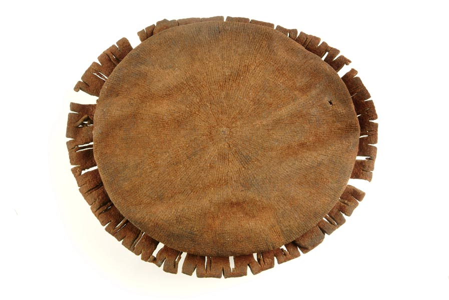 Boy's circular knitted cap with a brim decorated with slashes. The wool has turned brown with age. There are patches of the felted surface still remaining.