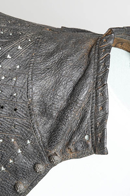 Leather jerkin (a short-sleeved jacket) decorated with slashes and holes cut through the leather.