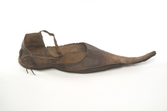 Brown leather shoe, shaped like a modern  pump but with a very long, pointed toe. There is an ankle strap from the front of the heel section.