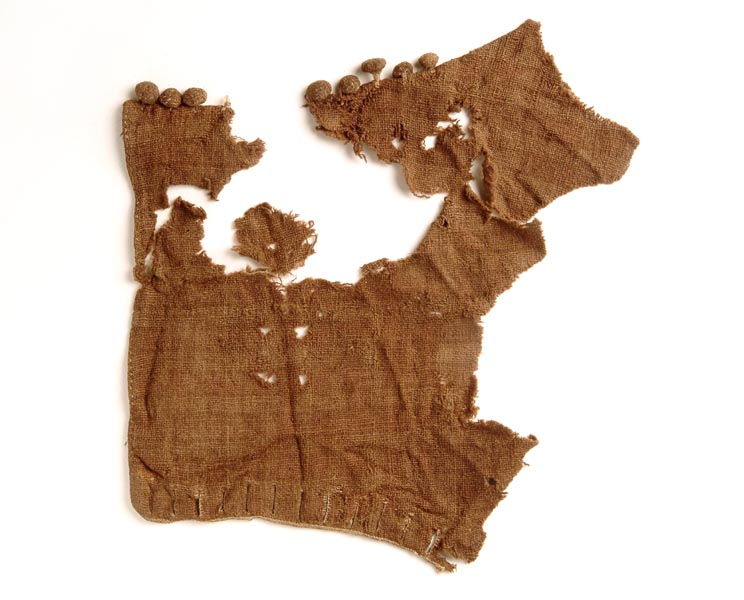 Fragment of woollen sleeve that is open and flat. There are 8 woollen buttons at the top and button holes at the bottom. The wool is discoloured and brown.